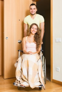 couple with woman in wheelchair near door